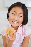 Portrait of a smiling young girl enjoying cookie