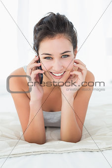 Beautiful smiling woman using mobile phone in bed