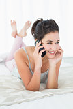 Beautiful woman using mobile phone in bed