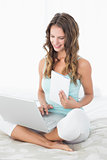 Woman using laptop as she holds a notepad in bed