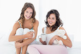 Smiling female friends with coffee cups in bed