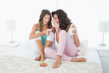 Relaxed female friends with coffee cups gossiping in bed