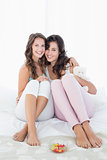 Cheerful female friends sitting on bed with arm around