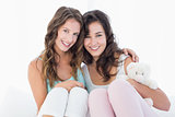 Female friends sitting on bed with arm around