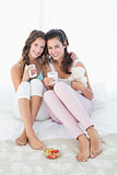 Cheerful young female friends with coffee cups in bed