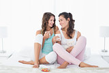 Young female friends with coffee cups in bed