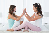 Happy female friends playing clapping game on bed