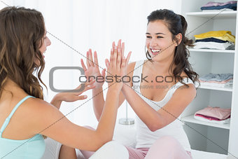 Happy female friends playing clapping game