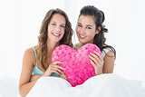Smiling female friends with heart shaped pillow in bed