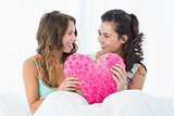 Female friends with heart shaped pillow in bed