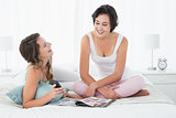 Female friends with magazine chatting in bed
