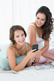 Smiling female friends reading text message in bed