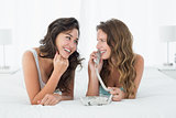 Relaxed young female friends using phone in bed