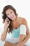 Smiling woman in tank top using mobile phone in bed