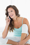 Woman in tank top using mobile phone in bed