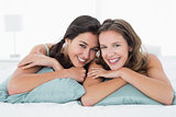 Smiling young female friends lying in bed