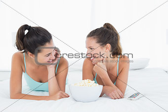 Smiling female friends with popcorn bowl lying in bed