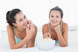 Smiling female friends eating popcorn in bed