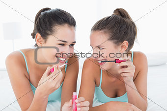 Two young female friends applying make-up in bed