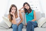 Unhappy friends not talking after argument at home