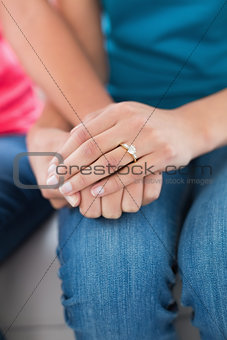 Close-up mid section of female friends holding hands