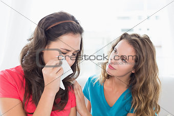Woman consoling a crying female friend at home