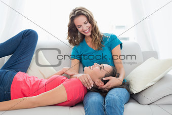 Female resting on friends lap in the living room