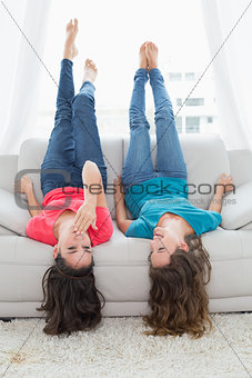 Smiling friends lying on sofa with legs in the air at home