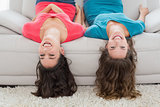 Female friends lying upside down on sofa at home