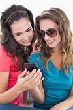 Female friends in sunglasses reading text message