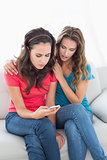 Upset female friends reading text message at home