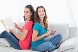 Smiling friends with book and digital tablet sitting at home