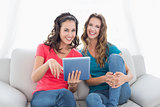Smiling female friends using digital tablet in the living room