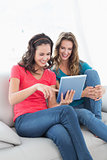 Female friends using digital tablet in the living room