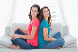Smiling female friends sitting back to back in the living room