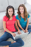Female friends using laptop in the living room