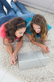 Female friends using laptop at home