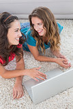 Two young female friends using laptop at home