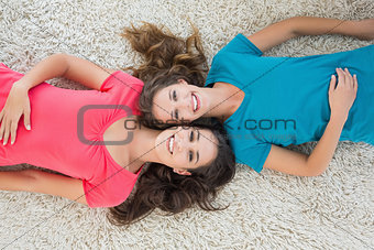 Portrait of two young female friends lying on rug
