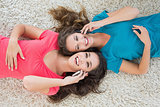 Two female friends lying on rug and using cellphone