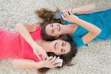 Two female friends lying on rug and text messaging