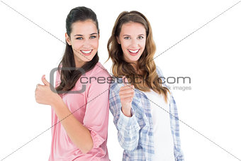 Portrait of two female friends gesturing thumbs up