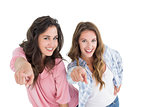 Female friends pointing against white background