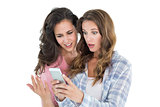 Shocked female friends looking at mobile phone