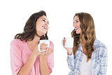 Cheerful friends chatting while drinking coffee