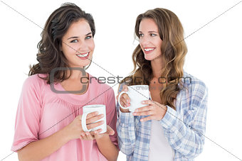 Two smiling young female friends drinking coffee