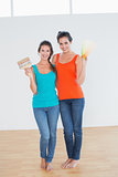Friends holding paint brush and color swatches in a new house