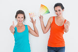 Female friends with color swatches gesturing thumbs up