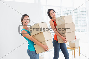 Female friends carrying boxes in in new house