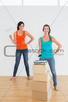 Female friends with paint brushes in a new house